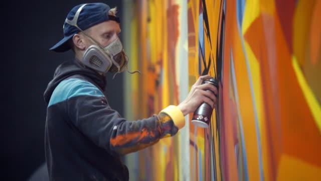 graffiti-künstler malen an der wand, innen - künstlerischer beruf stock-videos und b-roll-filmmaterial