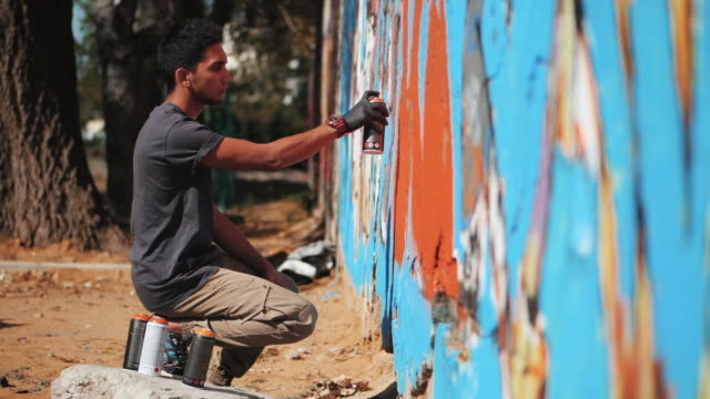 Graffiti Artist Painting With Aerosol. Man with spray bottle. Slow Motion. Young urban painter drawing colorful graffiti on the urban street wall at summer sunny day. Side view video