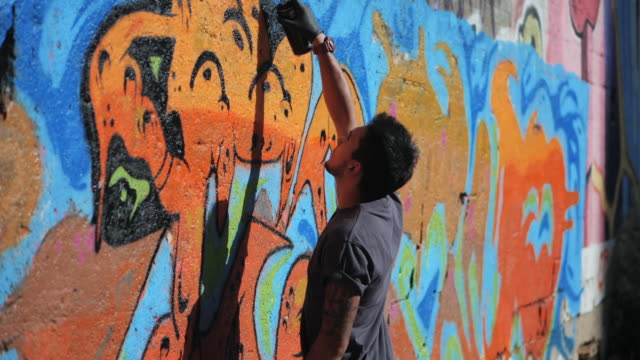 Graffiti Artist Painting With Aerosol. Man with spray bottle. Slow Motion. Young urban painter drawing colorful graffiti on the urban street wall at summer sunny day. Gimbal shot video