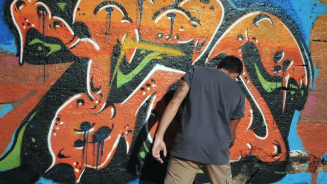 Graffiti Artist Painting With Aerosol. Man with spray bottle. Slow Motion. Young urban painter drawing colorful graffiti on the urban street wall at summer sunny day. Back view, overall plan video