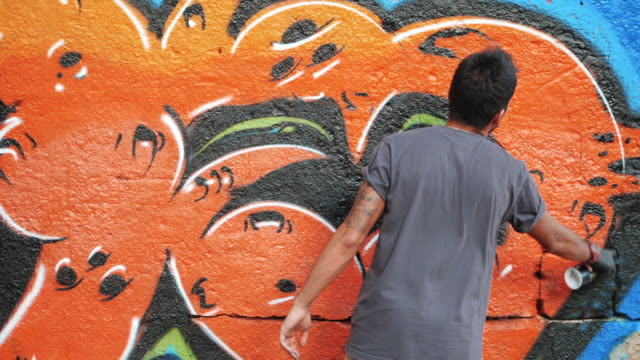 Graffiti Artist Painting With Aerosol. Man with spray bottle. Slow Motion. Young urban painter drawing colorful graffiti on the urban street wall at summer sunny day video