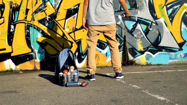 A graffiti artist prepares to use a yellow paint can. video