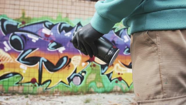 Grafitero sacudida puede con tinte en graffitis pared de fondo, cámara lenta, de cerca - vídeo