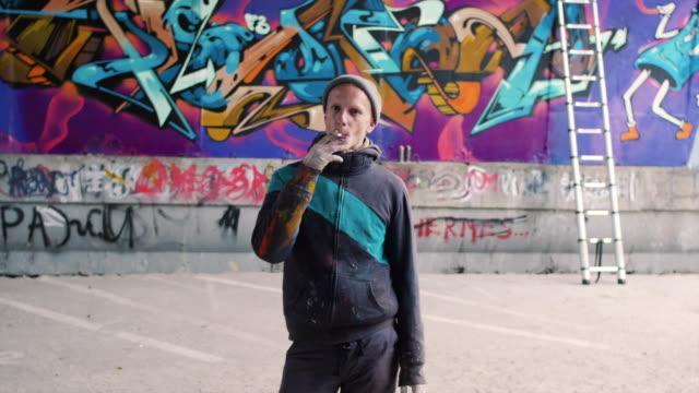 グラフィティ アーティスト喫煙タバコと彼の作品を見て - street graffiti点の映像素材/bロール