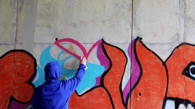 Graffiti Artist Spraying Graffiti on Wall Graffiti Artist Spraying Graffiti on Wall. mural stock videos & royalty-free footage