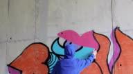 istock Graffiti Artist Spraying Graffiti on Wall 1150812709