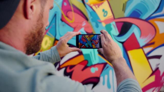 Graffiti artist taking photo of graffiti wall with phone 4k