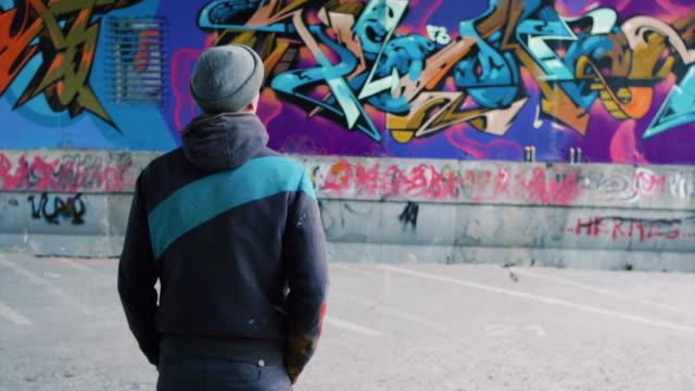 graffitikonstnär titta på hans arbete - väggmålning bildbanksvideor och videomaterial från bakom kulisserna