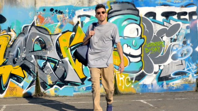 Graffiti artist with a bag on his shoulder is going away from the  wall covered with graffiti pictures. video