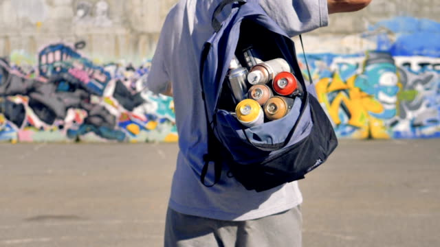 a graffitist puts on an open backpack full of paint cans. - viaggiare zaino in spalla video stock e b–roll