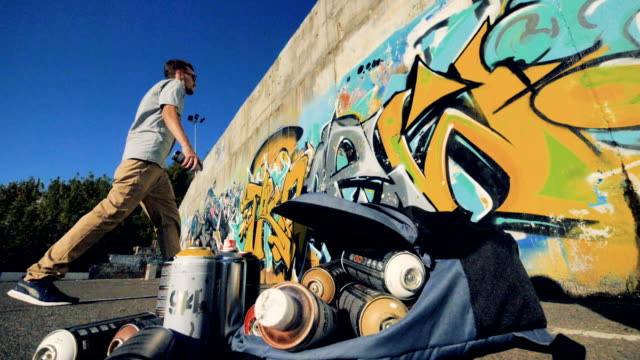 A graffitist works in the distance. video