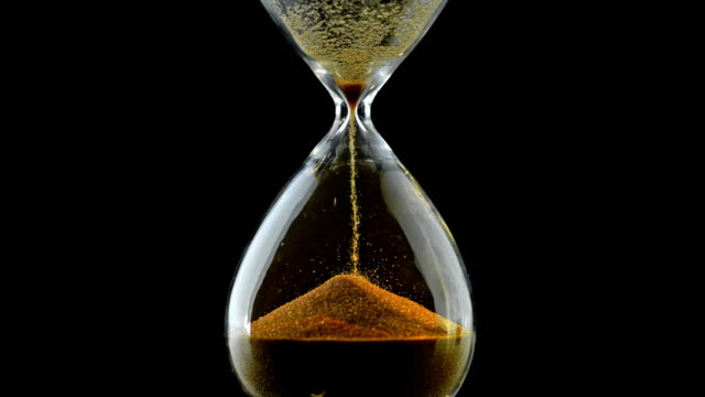 SLO MO LD Grains of golden sand falling through an hourglass Slow motion medium locked down shot of grains of golden sand falling through the neck of an hourglass against black background. Shot in Slovenia. instrument of time stock videos & royalty-free footage