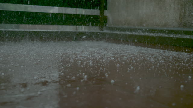 close up, dof: grains of graupel and rainwater cover the brown tiled balcony. - grandine video stock e b–roll