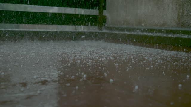 primo piano, dof: granelli di graupel e acqua piovana coprono il balcone piastrellato marrone. - portico video stock e b–roll