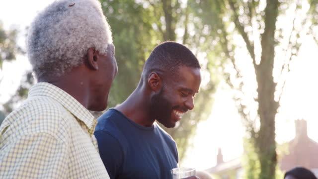 vídeos y material grabado en eventos de stock de abuelo habla con sus hijos y su nieto en barbacoa familiar - grilling