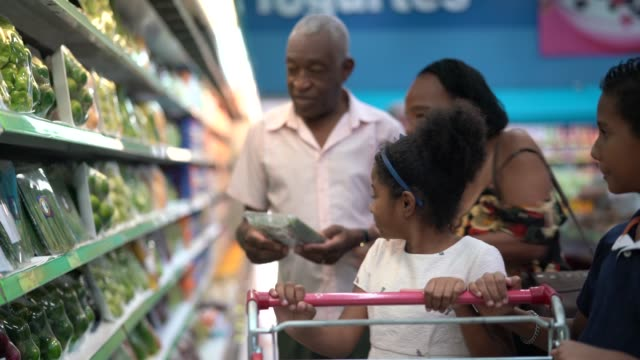 enkel und großeltern kaufen im supermarkt - supermarkt einkäufe stock-videos und b-roll-filmmaterial