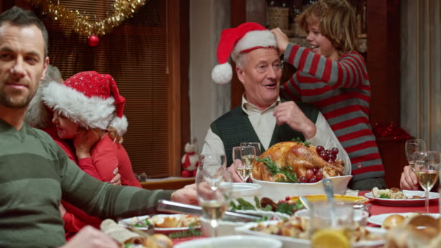 stockvideo's en b-roll-footage met grandchildren having fun with grandparents at the christmas table - kerst