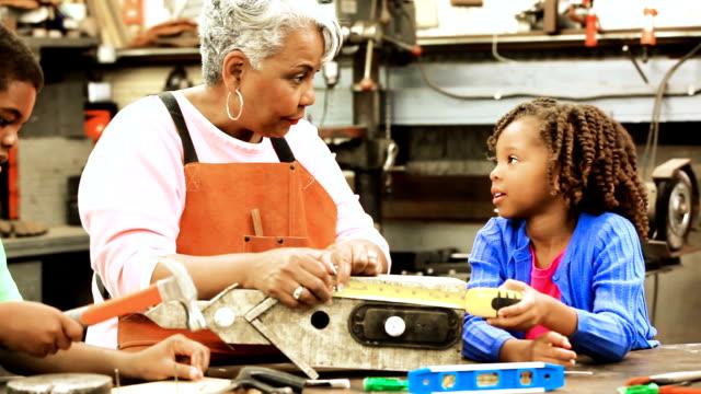 Grandchildren in workshop with active senior grandmother building birdhouses. video