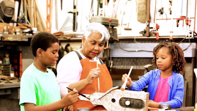 vídeos de stock, filmes e b-roll de netos de workshop com ativa avó sênior birdhouses de construção. - idosos ativos