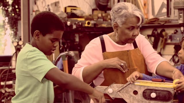 Grandchildren in workshop with active senior grandmother building birdhouses. video