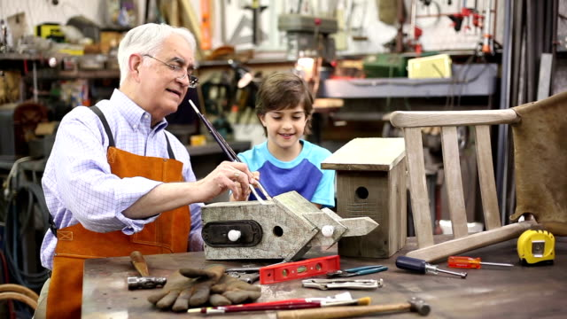 Grandchildren in workshop with grandfather repairing a birdhouse. video