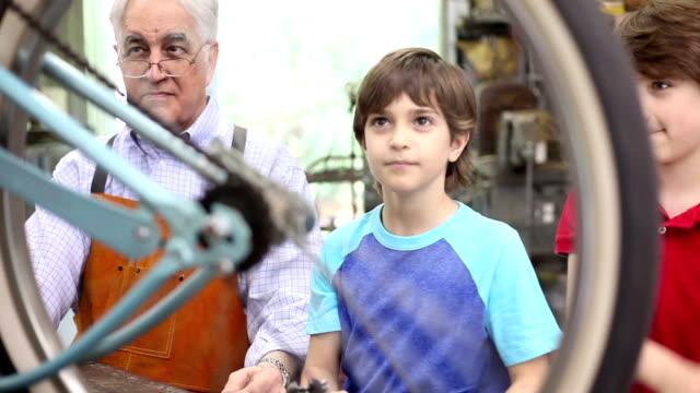 Grandchildren in workshop with grandfather repairing bicycle. video