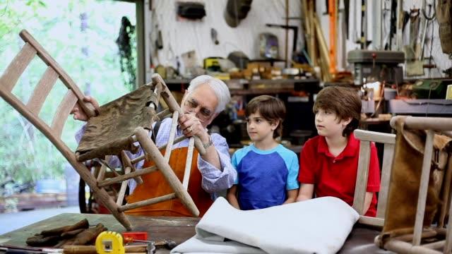 Grandchildren in workshop with grandfather reparing antique furniture. video