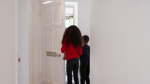 barnbarn som körs för att öppna dörren som morföräldrar anländer med presenter till jul besök - christmas gift family bildbanksvideor och videomaterial från bakom kulisserna