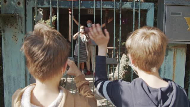 vídeos y material grabado en eventos de stock de nietos saludando a sus abuelos durante la cuarentena covid-19 - posición descriptiva