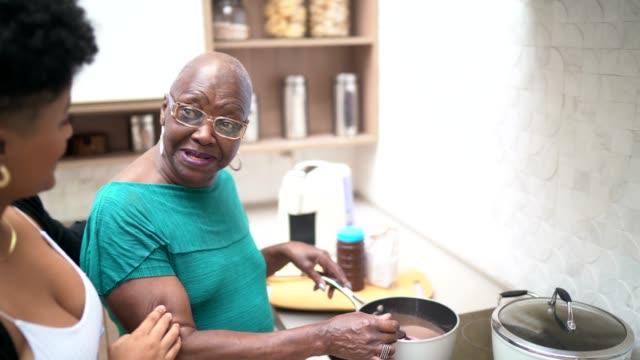 vídeos de stock, filmes e b-roll de neta e avó que cozinham junto - brigadeiro