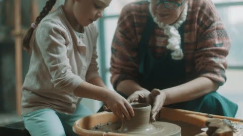 Granddaughter and grandmother doing pottery together Granddaughter and grandmother doing pottery together craft stock videos & royalty-free footage