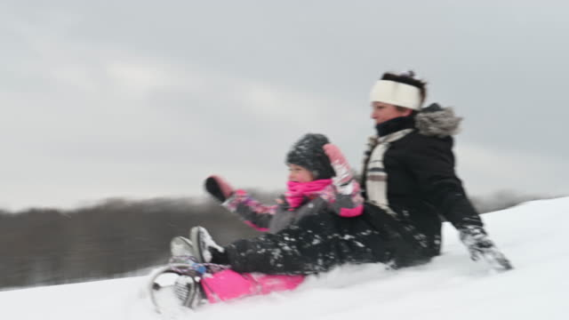 Granddaughter and Grandmother Playing on Snow Hill winter sport