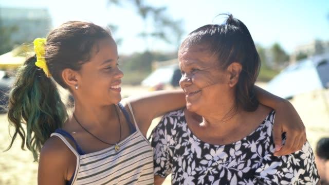 nipote e nonna sorridenti e abbracciate in spiaggia - nipote femmina video stock e b–roll