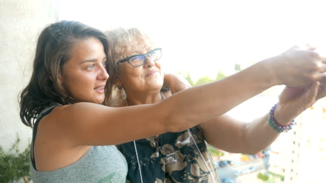 Granddaughter and her grandmother taking selfies together Medium side view shot of a young girl and her grand mother who are taking selfies / pictures together using a smart phone. They are both casually dressed. The scene plays out on a balcony in a city building during the day in Bourgas, Bulgaria. The footage is taken with Panasonic Lumix LX-100 camera. granddaughter stock videos & royalty-free footage