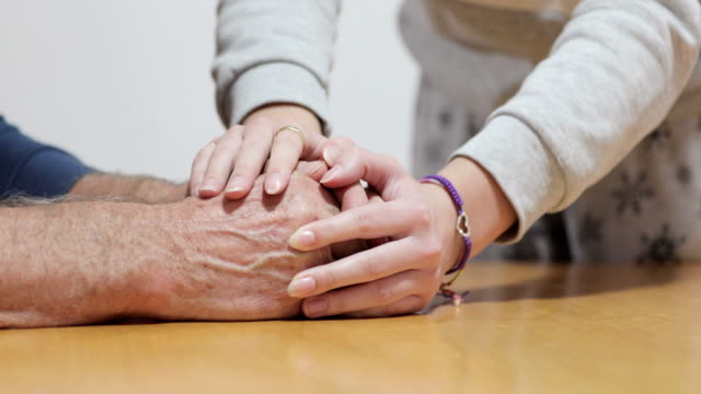 Granddaughter Calming Shaking Hands Of Grandfather With Parkinson's Disease video