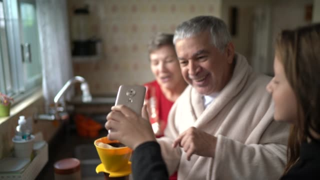granddaughter doing a video call while her grandfather doing a coffee at morning - video call with family video stock e b–roll