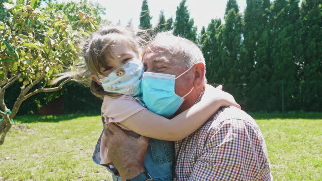 Granddaughter embracing her grandfather after a month not seen him during the pandemic Slow motion video of granddaughter embracing her grandfather after a few weeks without seen him for the pandemic. covid mask stock videos & royalty-free footage