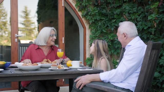 Granddaughter Enjoying Outdoor Breakfast with Grandparents
