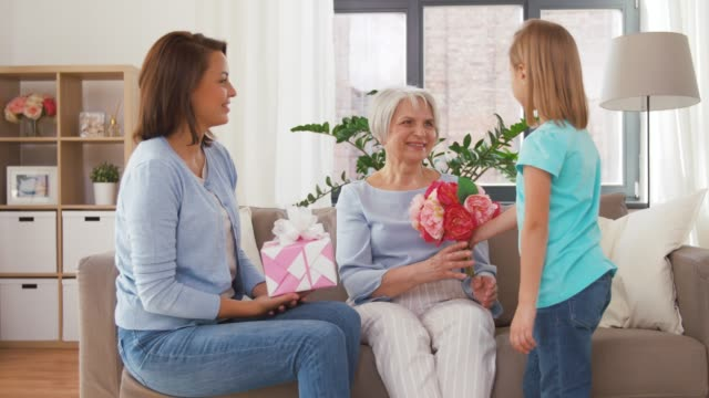 granddaughter giving flowers to grandmother