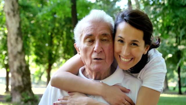 stockvideo's en b-roll-footage met kleindochter, verpleegkundige, zorg voor de ouderen, meisje (vrouw), grootvader, gelukkig, vrijheid, rennen in het park. - gezondheidszorg beroep