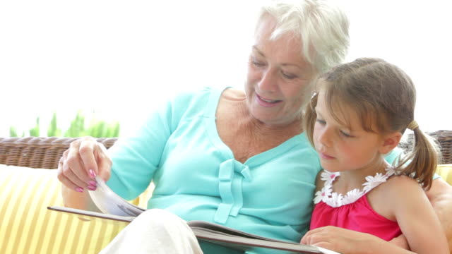 Granddaughter Reading Book With Grandmother Granddaughter sitting next to grandmother as they read a book together. Shot on Canon 5d Mk2 with a frame rate of 30fps granddaughter stock videos & royalty-free footage