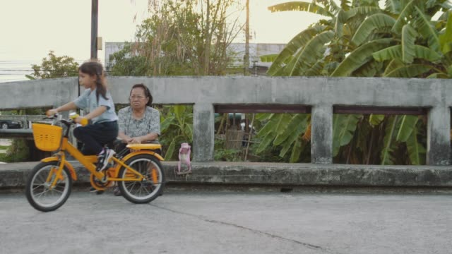 Granddaughter Riding a Bike While Grandmother Watching Over