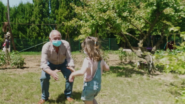 stockvideo's en b-roll-footage met kleindochter die haar grootvader tijdens de pandemie in werking stelt - omhelzen