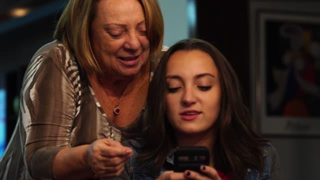 enkelin mit mobil mit großmutter zu hause - klatsch stock-videos und b-roll-filmmaterial