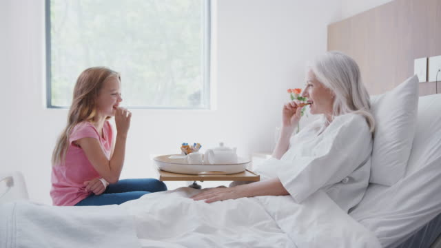 granddaughter visiting grandmother in hospital bed for afternoon tea - nipote femmina video stock e b–roll