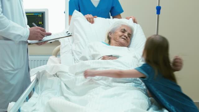 barnbarn besöker gamla kvinnan i sjukhuset rum - hospital studio bildbanksvideor och videomaterial från bakom kulisserna