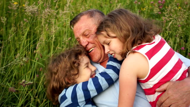 Grandfather and grandchildren, a boy and a girl, a brother and a sister rest on a summer glade. Grandchildren gaily hug grandfather, lay in the grass and laugh. Happy Family Vacation