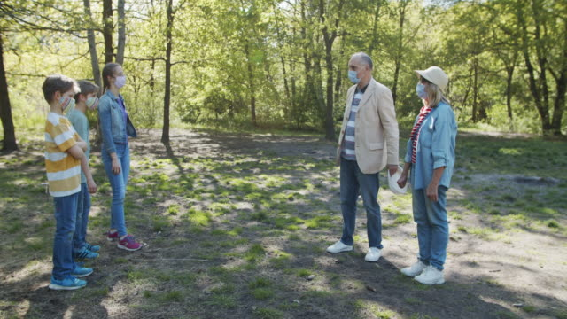 stockvideo's en b-roll-footage met grootvader en kleinkinderen die in park tijdens covid-19 pandemie samenkomen - sociale bijeenkomst