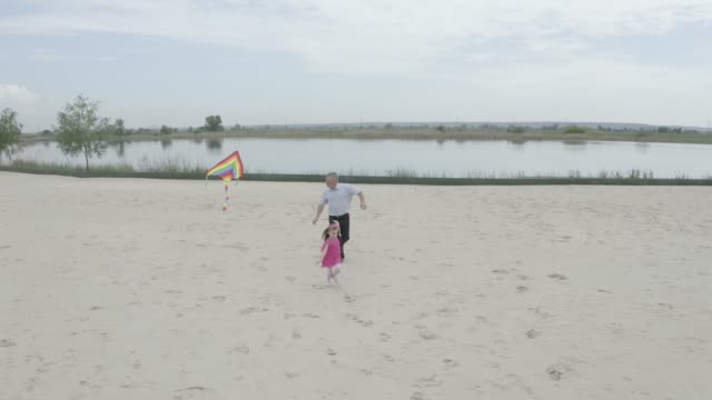 Grandfather and granddaughter launch a kite on the beach at the lake. Filming from the air. 4K Slow Mo Grandfather and granddaughter launch a kite on the beach at the lake. Filming from the air. granddaughter stock videos & royalty-free footage