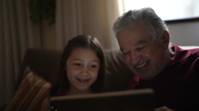 grandfather and granddaughter on a video call with a digital tablet at home - vivere semplicemente video stock e b–roll
